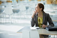 Businesswoman daydreaming at cafeteria table