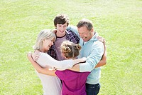 Smiling family hugging in circle on grass