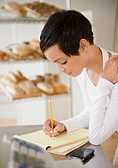 Mixed race woman in bakery writing in notepad