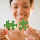 Mixed race woman holding green jigsaw puzzle pieces