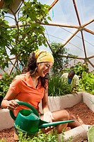 Ecuadorian woman watering plants in greenhouse