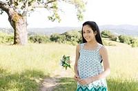 Hispanic girl holding pinwheel in field