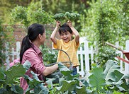 Asian mother and son playing in garden