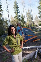 Couple camping and standing outside tent