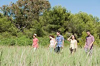 Young friends walking through field (thumbnail)