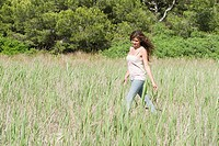 Young woman walking through field (thumbnail)