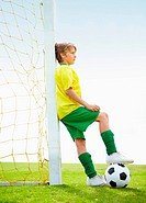 Soccer kid stands with one foot on ball