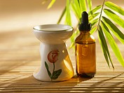 Essential oil burner and bottle on bamboo mat