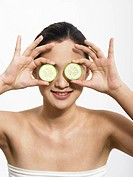 A woman holding cucumber slices on her eyes
