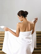 Young Asian girl wrapping towel around herself