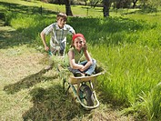Boy pushing wheelbarrow with girl in it