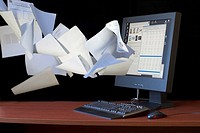 Papers flying into a flat screen computer monitor  Indicates the idea of the paperless office, suggesting how computers can help people organize their...