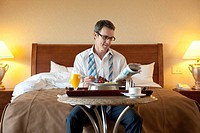 Businessman in Hotel Room with Breakfast