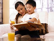 Mother reading book with son