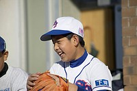 Boy in baseball uniform smiling