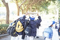 Boys in baseball uniform walking, holding backpacks
