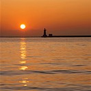 Sunrise Over the Ocean and the Silhouette of a Lighthouse and Pier. Hokkaido, Japan