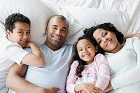 Family lying in bed