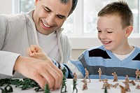 Father and son playing with toy soldiers