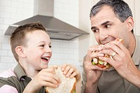 Father and son eating sandwiches