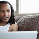 Man relaxing in bed using a laptop