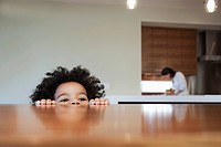 Little boy looking over the edge of a table (thumbnail)