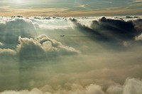 Sunbeams shining on clouds and jet (thumbnail)