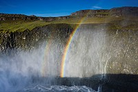 Rainbow and mist above river in canyon