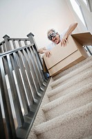 Man preparing to ride down stairs in box