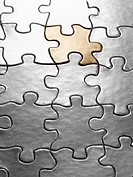 One gold puzzle piece in jigsaw puzzle