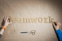 People forming the word teamwork on paper