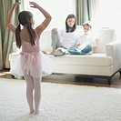 Girl practicing ballet for family