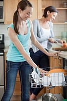 Mother and daughter washing dishes