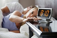 Woman hitting snooze on alarm clock (thumbnail)