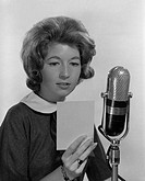 Young woman reading into microphone