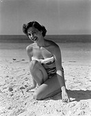 Portrait of pin_up girl wearing bikini, crouching on sandy beach