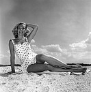 Young woman wearing swimsuit sitting on beach