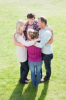 Smiling family hugging in a circle on grass