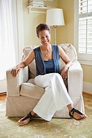 Mixed race woman sitting in armchair