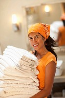 Hispanic woman carrying stack of towels