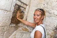 Woman inserts her hand at a handprint on a wall, Station V, Way of the cross, Via Dolorosa, Jerusalem, Israel, Middle East