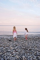 Rearview 6 year girl and 5 year girl standing on stony beach throwing stones into sea