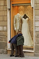 Two children embracing in front of shop window with bride´s gown, Grosseto, Tuscany, Italy, Europe