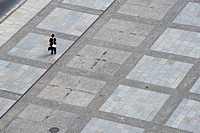A woman standing alone on an urban plaza