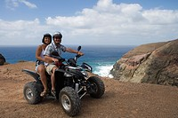 Couple on a quad all_terrain vehicle near Ponta da Canaveira, Porto Santo, near Madeira, Portugal