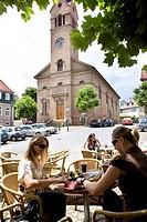 Pavement cafe at market square, parish church in background, Kusel, Rhineland_Palatinate, Germany