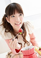 Young woman eating chocolate fondue