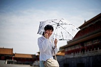 A Chinese girl uses her mobile phone as he walks with an umbrella at the Forbidden City in Beijing With approximately 650 million subscribers, China i...