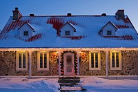 Illuminated two_storied Canadiana style residential home decorated with a Christmas wreath and lights at dusk, Laval, Quebec, Canada