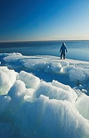 a man looks out over melting ice, along Lake Winnipeg, Manitoba, Canada